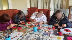 Campania ARBD residents hand painting poppies for their Armistice Day tribute