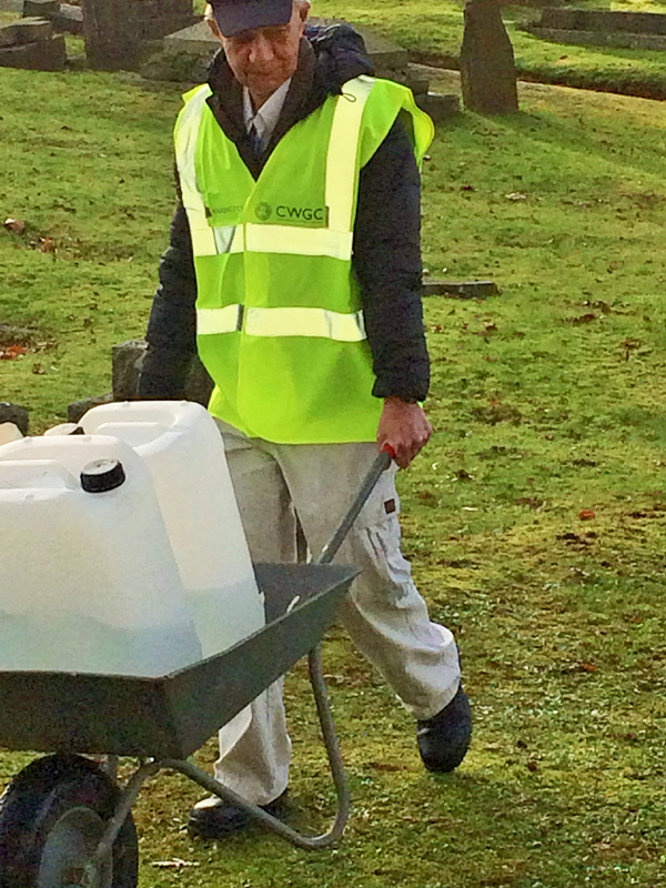 Vane Hill resident carrying a wheelbarrow of water to clean the war graves as part of the 'Eyes On, Hands-On' project run by The CWGC