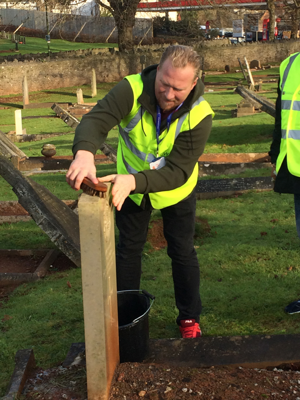 Vane Hill ARBD care home support worker cleaning war graves as part of a new 'Eyes On, Hands-On' project run by The CWGC