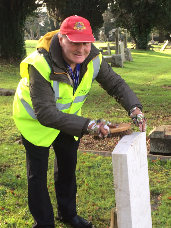 Vane Hill ARBD care home resident cleaning war graves as part of a new 'Eyes On, Hands-On' project run by The CWGC