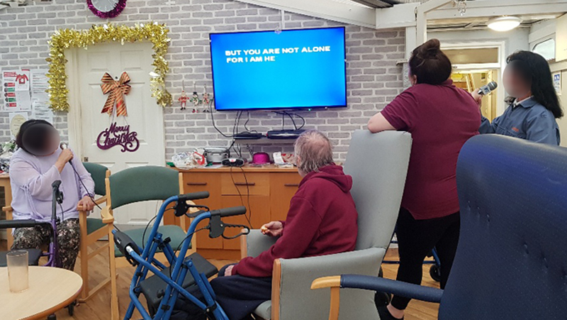 Campania ARBD care home residents singing Karaoke as part of their Christmas celebrations