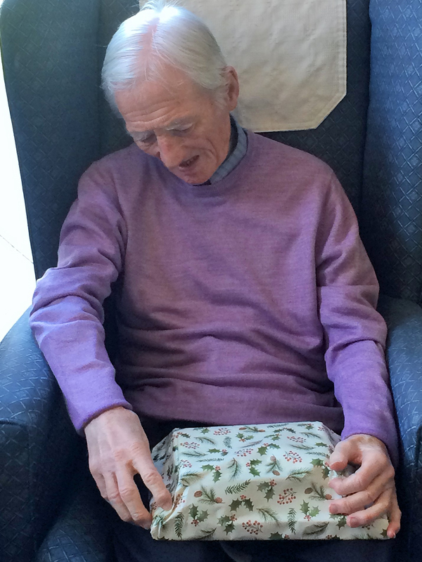 Vane Hill ARBD resident opening his present on Christmas Day