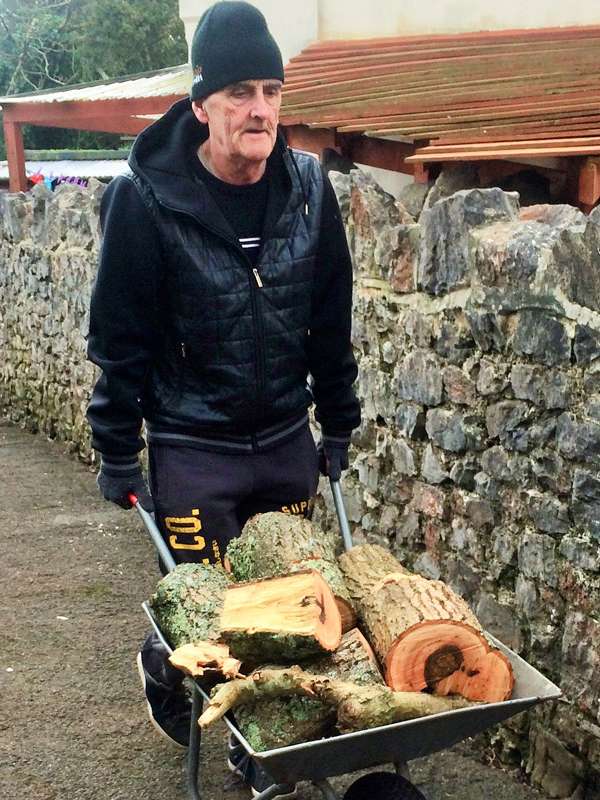 Vane Hill ARBD care home resident moving wheelbarrow full of logs for their neighbour